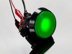 angled shot of illuminated large green arcade button with LED.