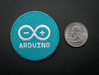 Circular embroidered badge in turquoise with the word ARDUINO and their infinity logo + - in white.