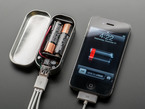 Assembled MintyBoost kit in mint tin with top open, charging an iPhone with low battery.