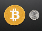 Circular embroidered badge in orange with stylized B Bitcoin logo in white.