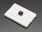 Angled shot of red on-off power button on half-size breadboard.
