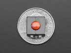 Top-down shot of red on-off power button on top of US quarter