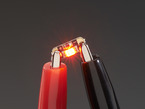 Single LED sequin PCB attached to two alligator clips, glowing red