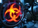 Spoke POV long-capture image showing bio-hazard logo in red lights on bike wheel.