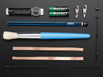 Collection of loose components in kit: assembled PCB, pencil, brush, copper tape and other parts.