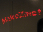 "Mini POV long-capture image showing ""MakeZine!"" in red lights."
