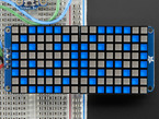 """Close-up of Soldered and assembled 16x8 1.2"""" LED Matrix + Backpack - Ultra Bright Square Blue LEDs on a breadboard. The LED Matrices display a smiling emoji and a frowning emoji."""