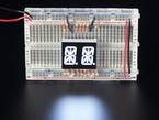 White Dual Alphanumeric Display module wired to breadboard, all segments lit