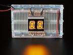 Yellow Dual Alphanumeric Display module wired to breadboard, all segments lit