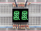 green Dual Alphanumeric Display module wired to breadboard, all segments lit