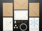 Top view of three letter envelopes, two holiday greeting cards, conductive copper tape, coin cell batteries, circuit LED stickers, and star pins.