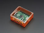 Angled shot of orange Raspberry Pi Model A+ Case with clear lid.