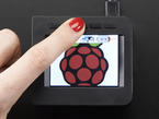 """Top-down shot of assembled 2.4"""" PiTFT HAT. A red manicured finger presses a button above the display which shows a raspberry logo."""