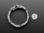 Stainless Steel multitool bracelet  next to quarter