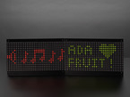 powered on 32x16 Red Green Dual Color LED Dot Matrix - 7.62mm Pitch. The matrix display has red and green music notes and Adafruit and a heart symbol.