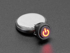 angled shot of mini red illuminated push-button powered by a coin cell battery.