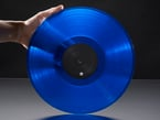 Shot of a hand holding up a translucent blue record disc.