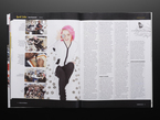 Opened magazine page to editorial interview with a woman with short pink hair. She wears white and black amidst a background of round dev boards.