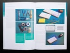 Open book spread featuring maker tools, including breadboards, pliers, scissors, conductive thread, and more.