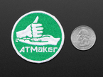 Circular embroidered badge with hands motioning for Rock with the words AT MAKER in white, over a green background.