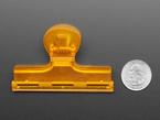 Back of plastic orange clip next to US quarter for scale.