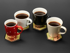Four different types of mugs with black coffee on top of PCB coasters.