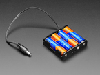 Angled shot of 4 x AA battery holder with 2.1mm plug filled with four AA batteries.