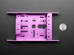 Bottom of purple aluminum metal robot chassis with many holes and mounting tabs.