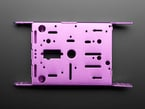 Top of purple aluminum metal robot chassis with many holes and mounting tabs.