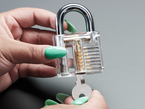 Hands holding clear padlock and opening with a small key.