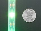 Detail of top of lit LED strip next to quarter