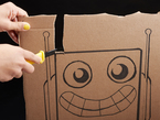 Person cutting out robot shape from cardboard