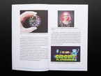 Open book spread featuring a round dev board with rainbow LEDs, a white woman with glasses and pink hair, and Circuit Playground, animated electrical component characters.