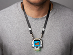 lanyard shown being worn around neck against grey t-shirt holding skull shaped circuit board