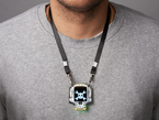 lanyard shown being worn around neck against grey t-shirt holding skull shaped circuit board with screen.