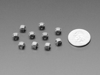 Angled shot of ten 6mm black mini soft touch pushbutton switches next to US quarter.