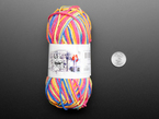 Top-down shot of a bundle skein of rainbow-colored yarn next to US quarter.