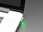 Tomu plugged into macbook USB port, glowing green.