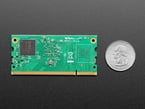 Top of Raspberry Pi Compute Module showing RAM and empty FLASH chip spot, next to Quarter