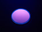 Angled shot of round purple disc of fluorescent paint under black light.