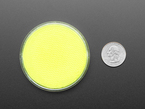 round yellow disc of fluorescent paint next to US quarter.