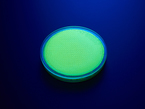 round yellow disc of fluorescent paint under black light.