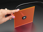 Hand holding acrylic piece with installed USB A Jack to Micro USB B Jack Round Panel Mount Adapter