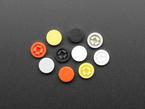 topdown shot of 10 plastic button caps colored reddish-orange, yellow, white, and black.
