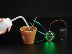Person watering sprouts with a Circuitry water sensor attached