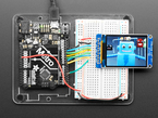 TFT breakout wired up on breadboard to Arduino, showing colorful image of friendly robot