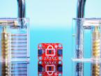 Adafruit Infineon Trust M Breakout Board next to two clear padlocks