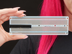 A woman with pink hair holding an assembled Adafruit Perma-Proto 40-Pin Raspberry Pi Breadboard PCB.