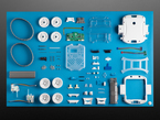 Kit component shot with many plastic pieces, wheels, motors and other hardware.