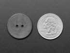 Black resin button with two holes for sewing next to quarter